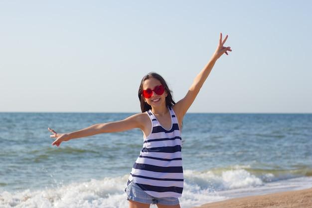 Meisje met een bril in de vorm van een hart tegen de achtergrond van de zeelucht die vredesteken met beide handen toont