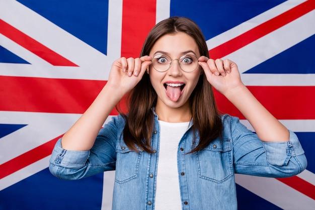 Meisje met een bril op de britse achtergrond van de strepenvlag