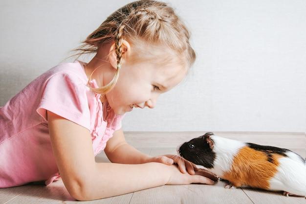 Meisje met een cavia in haar armen, op een witte muur. veel plezier en plezier