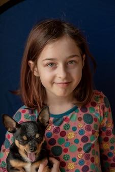 Meisje met een chihuahua. meisje met chihuahua. meisje met haar huisdier in haar armen. chihuahua in zwartbruin-witte kleur. kinderen zijn dol op hun dieren. meisje en chihuahua. kinderen zijn dol op hun dieren