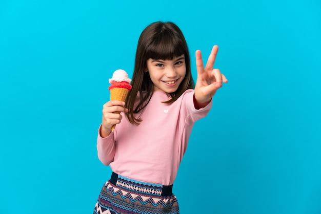Meisje met een cornetroomijs dat op blauwe muur wordt geïsoleerd die en overwinningsteken glimlacht toont