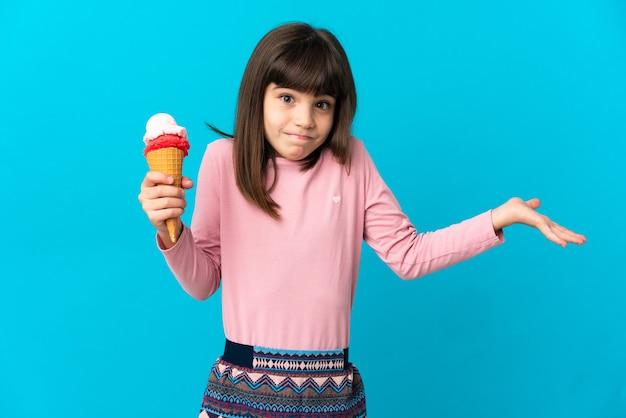 Meisje met een cornetroomijs dat op blauwe muur wordt geïsoleerd die twijfels heeft terwijl het opheffen van handen