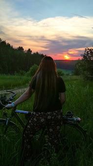Meisje met een fiets bij zonsondergang