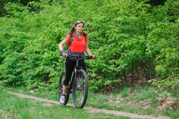 Meisje met een fiets in het bos