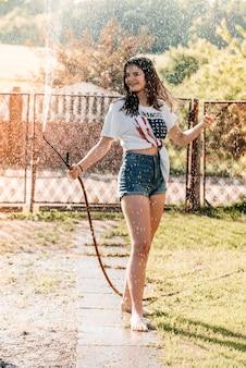Meisje met een fontein in de tuin bij zonsondergang. hete zomer, nat shirt. amerikaanse vlag.