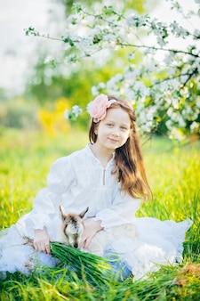 Meisje met een geit zitten in het gras in een weelderige appelboomgaard