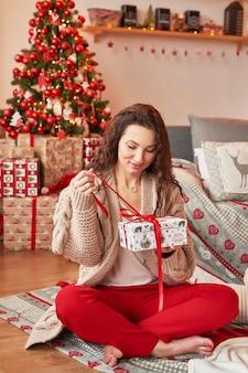 Meisje met een geschenk thuis in het nieuwe jaar interieur