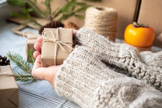 Meisje met een geschenk verpakt met haar eigen handen, close-up. kerstdecoratie, ontwerp van een geschenkdoos voor kerstmis gemaakt van natuurlijke materialen. de sfeer van het nieuwe jaar, voorbereiding op kerstmis.