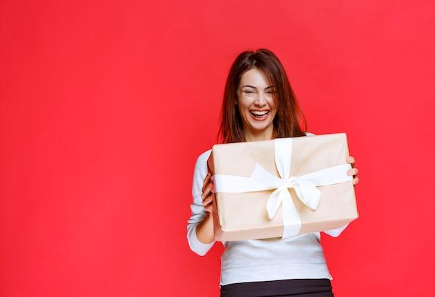 Meisje met een geschenkdoos en ziet er verrast en positief uit.