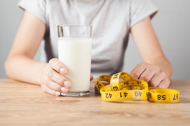 Meisje met een glas melk en meetlint