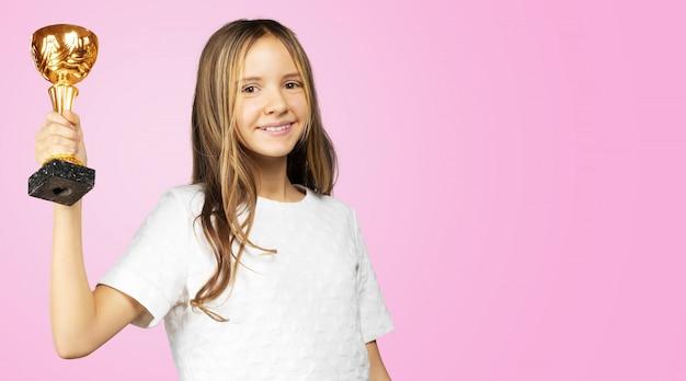 Meisje met een gouden trofeekop op roze achtergrond