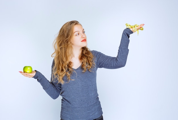 Meisje met een groene appel in de ene hand en een meetlint in de andere.