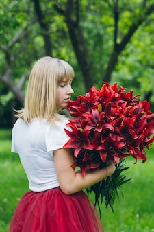 Meisje met een groot boeket paarse lelies