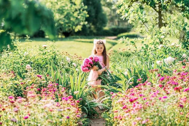 Meisje met een groot boeket pioenrozen. een kind loopt in de zomer in het park met bloemen.