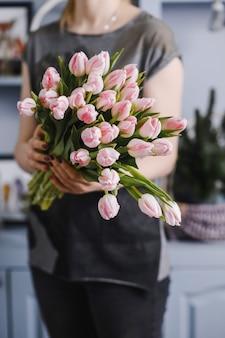Meisje met een groot boeket tulpen in haar handen.