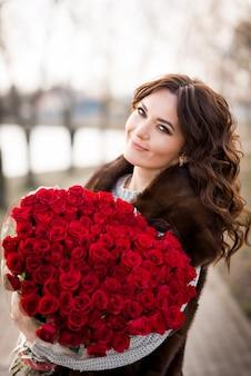 Meisje met een groot boeket van rode rozen. 101 rozen in een boeket