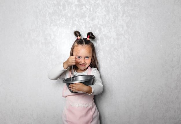 Meisje met een grote meel opkloppen, zelf pannenkoeken bakken