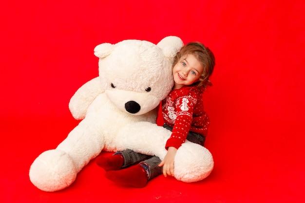 Meisje met een grote teddybeer in winterkleren op een rode achtergrond, ruimte voor tekst