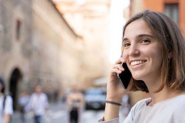 Meisje met een halve manen en een doorboorde neus lacht en praat met haar mobiele telefoon