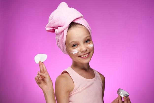 Meisje met een handdoek op haar hoofd cosmetica decoratie close-up paarse achtergrond