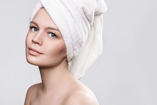 Meisje met een handdoek op het hoofd op een witte ondergrond die naar de voorkant kijkt, haar haar gewikkeld in een handdoek Premium Foto