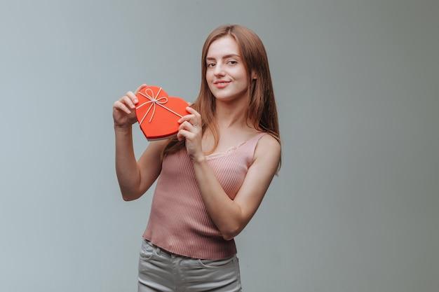 Meisje met een hart geschenkdoos op grijze achtergrond