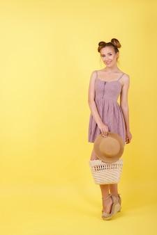 Meisje met een hoed en een strozak op een gele ruimte. zomerstemming