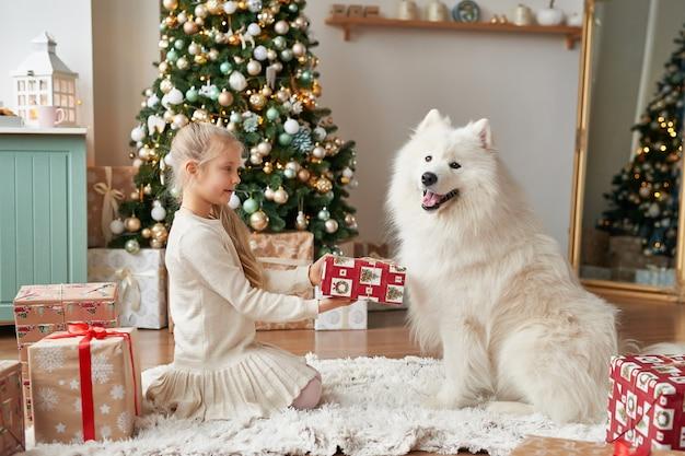 Meisje met een hond dichtbij de kerstboom op de kerstmisscène