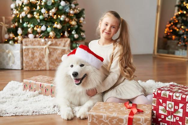 Meisje met een hond in de buurt van de kerstboom op de achtergrond van kerstmis