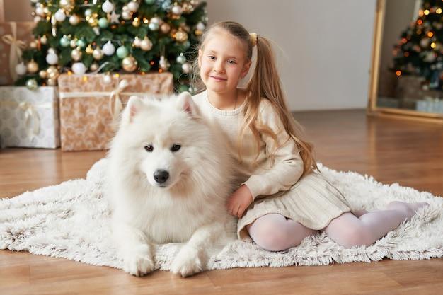 Meisje met een hond in de buurt van de kerstboom