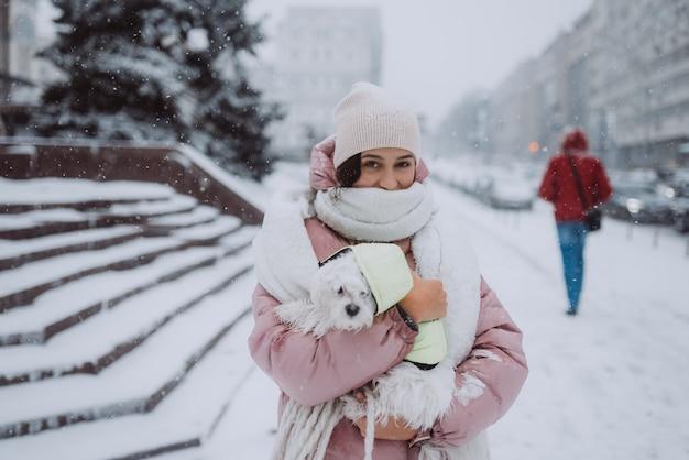 Meisje met een hond in haar armen op een straat in de stad sneeuw valt snow