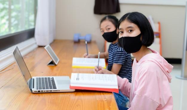 Meisje met een hygiënemasker, thuis studeren vanaf een computerscherm. thuisonderwijs