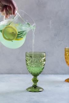 Meisje met een karaf in haar hand giet verfrissende limonade, mojito met citroen en munt in een gesneden glas.