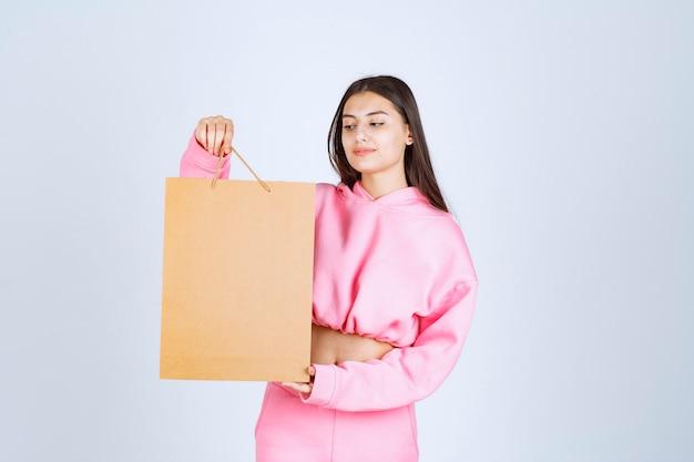 Meisje met een kartonnen boodschappentas en ernaar te kijken.