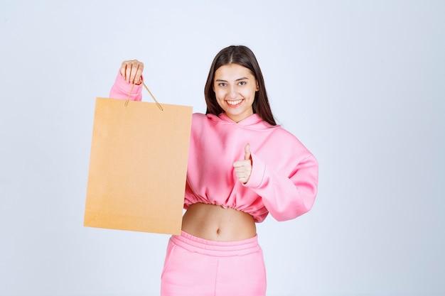Meisje met een kartonnen boodschappentas en opgewonden.