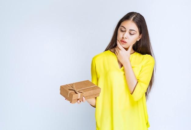 Meisje met een kartonnen geschenkdoos en ziet er in beslag genomen of bedachtzaam uit.
