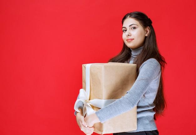 Meisje met een kartonnen geschenkdoos omwikkeld met wit tule lint.
