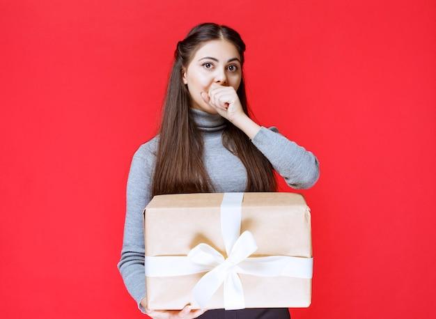 Meisje met een kartonnen geschenkdoos ziet er doodsbang en moe uit.