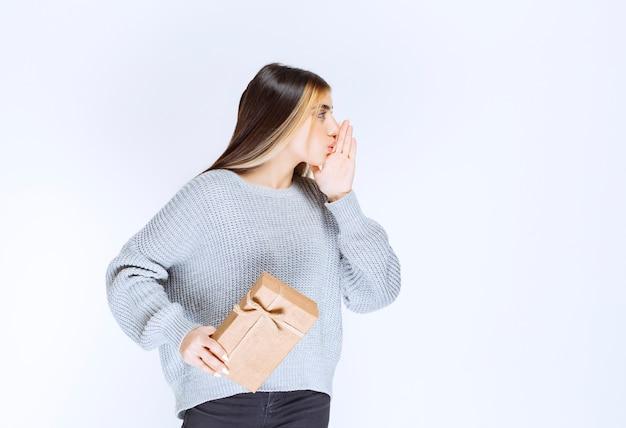 Meisje met een kartonnen geschenkdoos ziet er verward en opgewonden uit.