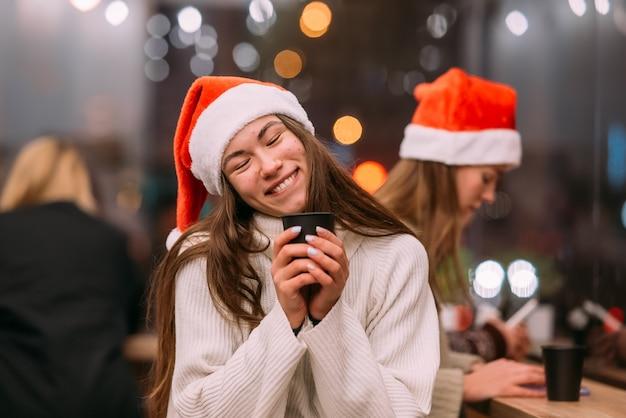 Meisje met een kerstmuts die in de coffeeshop zit en koffie drinkt