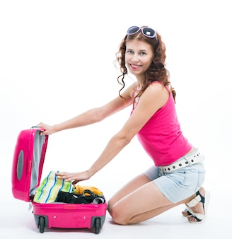 Meisje met een koffer die op witte achtergrond gaat reizen