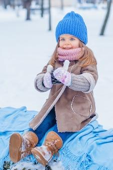 Meisje met een kopje in zijn handen in het park tegen de achtergrond van de sneeuw in het park