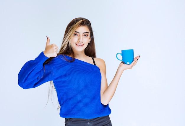Meisje met een kopje koffie en genieten van de smaak.
