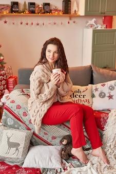 Meisje met een kopje marshmallow in het interieur van het nieuwe jaar thuis