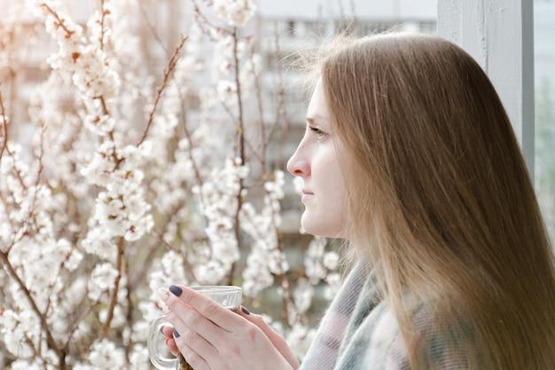 Meisje met een kopje thee staan bij het raam en kijkt in de verte. tot bloei komende boom op de achtergrond