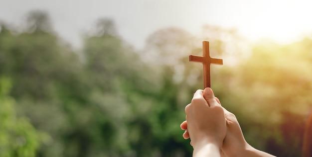 Meisje met een kruis om te bidden god zij dank prijst de heer met buitenachtergrond, bid, pasen en goed vakantieconcept