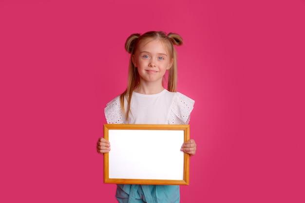 Meisje met een leeg frame, glimlachend plaats voor tekst studio op een roze