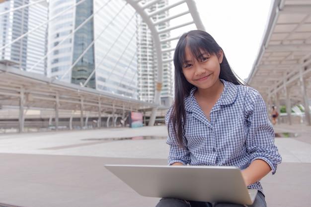 Meisje met een macbook-apparaat met een moderne grote stad