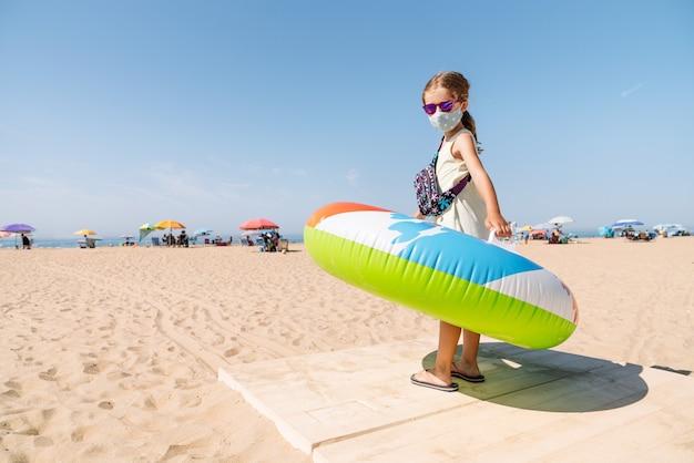 Meisje met een masker op haar gezicht en een bril die over een pad naar het strand loopt met een kleurrijk opblaasbaar matraswiel op haar armen om te genieten van een vakantie te midden van de coronaviruspandemie van covid 19