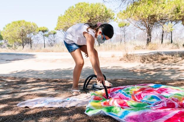 Meisje met een masker op haar gezicht en een zonnebril die de inflator in haar hand houdt om een kleurrijke opblaasbare matraslolly op te blazen om te genieten van een vakantie te midden van de coronavirus-pandemie covid 19